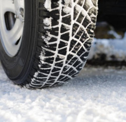 Snow covered tyre of a small SUV on a snowy road